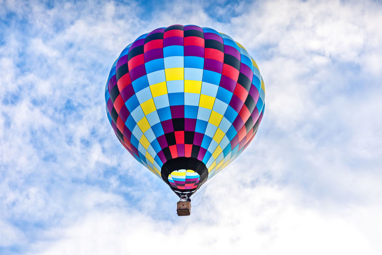 Single, colorful hot-air balloon high in the sky