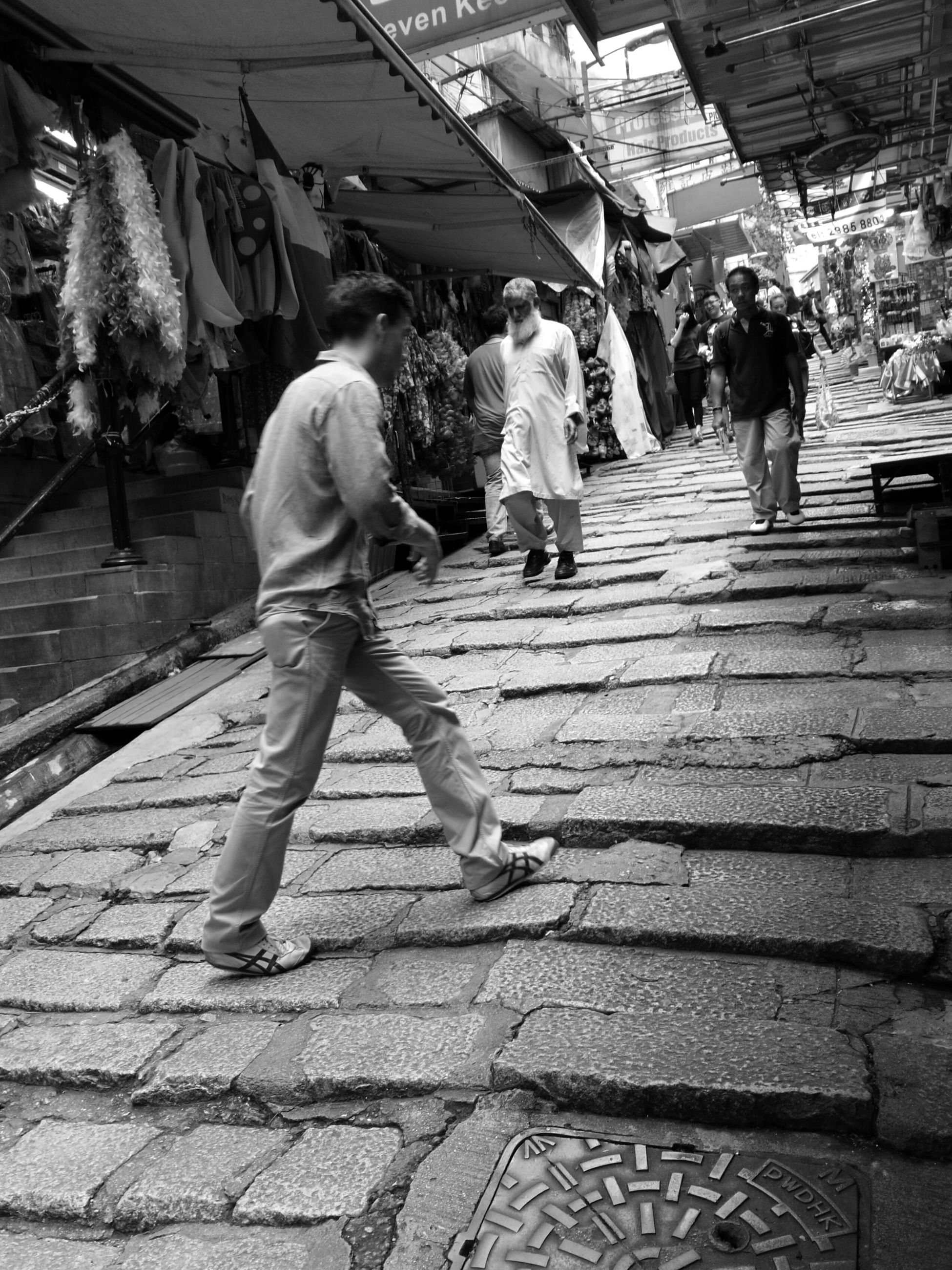 lifestyles, men, person, full length, leisure activity, walking, casual clothing, togetherness, large group of people, rear view, city life, street, medium group of people, steps, outdoors, boys, market, city