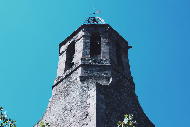 Low angle view of weather vane on tower against clear sky