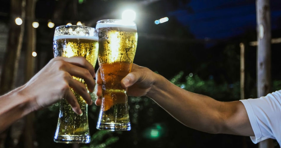 Cropped hands of friends toasting beer glasses