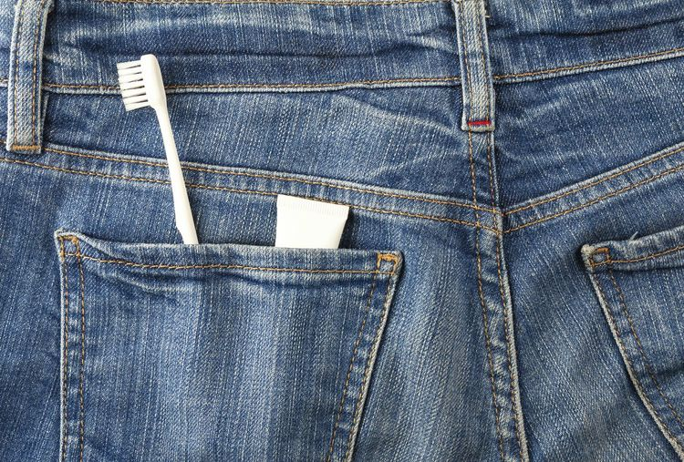 Close-Up Of Toothbrush With Tube In Denim Jeans Pockets