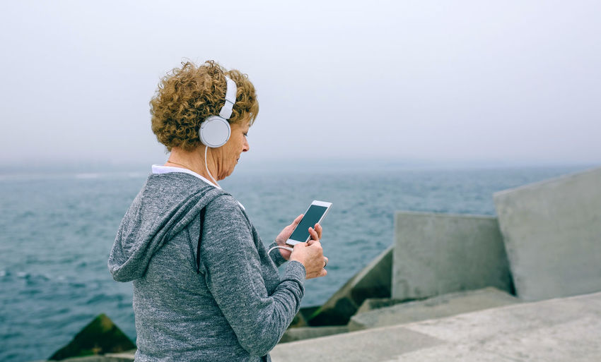 Woman using mobile phone while standing at beach against sky