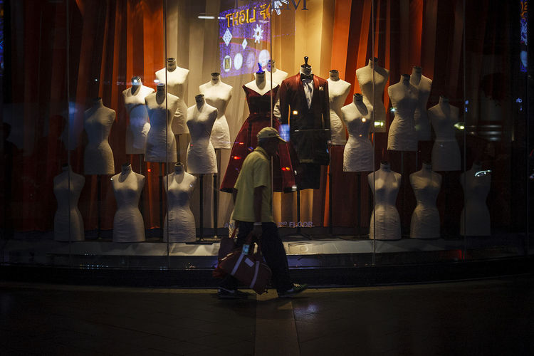 Rear view of people standing in illuminated store