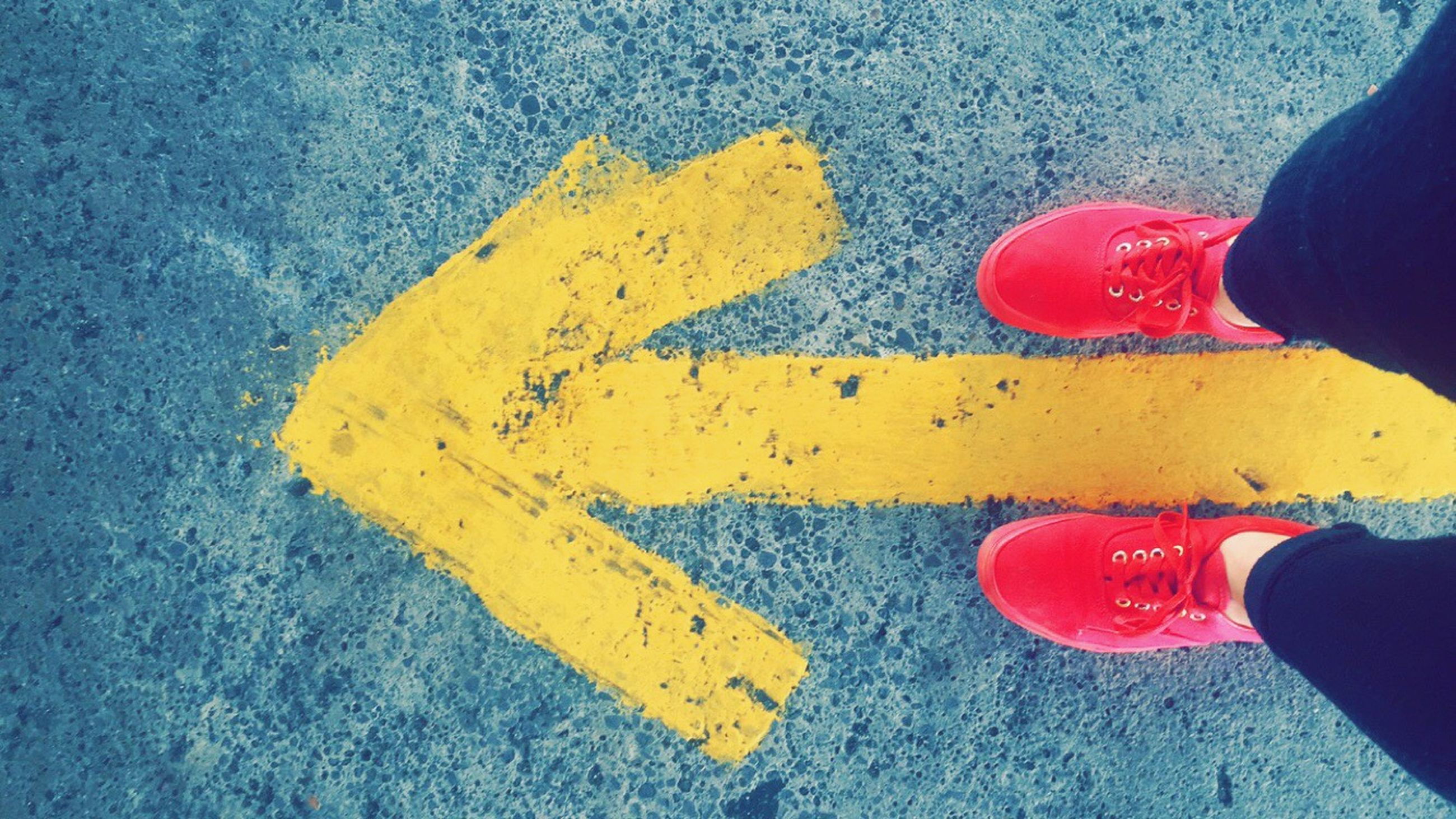 low section, person, personal perspective, lifestyles, shoe, street, leisure activity, men, high angle view, standing, unrecognizable person, part of, yellow, human foot, road marking, road, footwear
