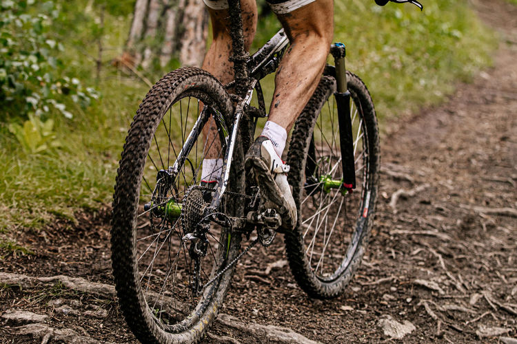 Low section of man riding bicycle on dirt road