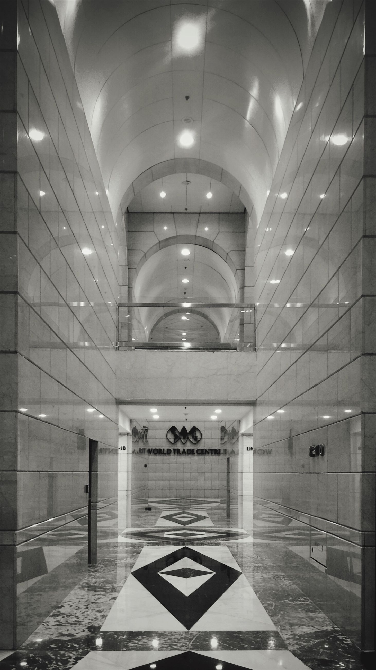 indoors, ceiling, illuminated, interior, architecture, corridor, arch, built structure, lighting equipment, empty, flooring, absence, the way forward, tiled floor, door, subway, wall - building feature, tunnel, diminishing perspective, tile