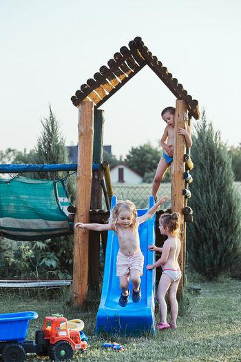 Siblings enjoying at yard against sky