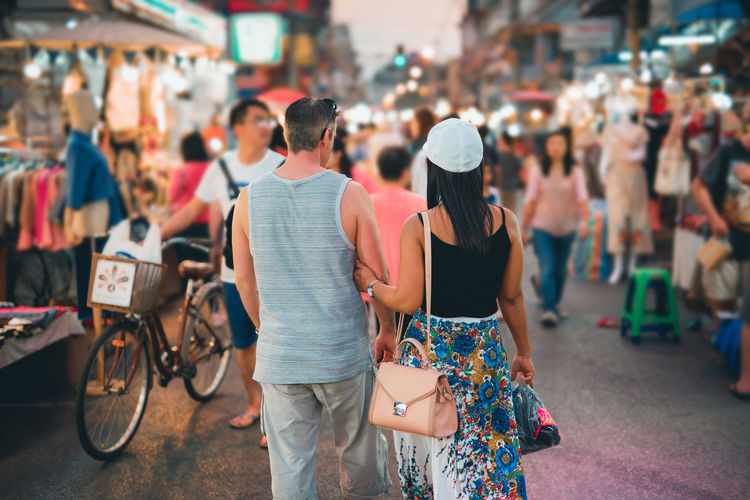 Backside of couple local travel and shopping at thailand night market