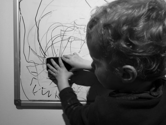 Cropped Image Of Girl Scribbling On White Board