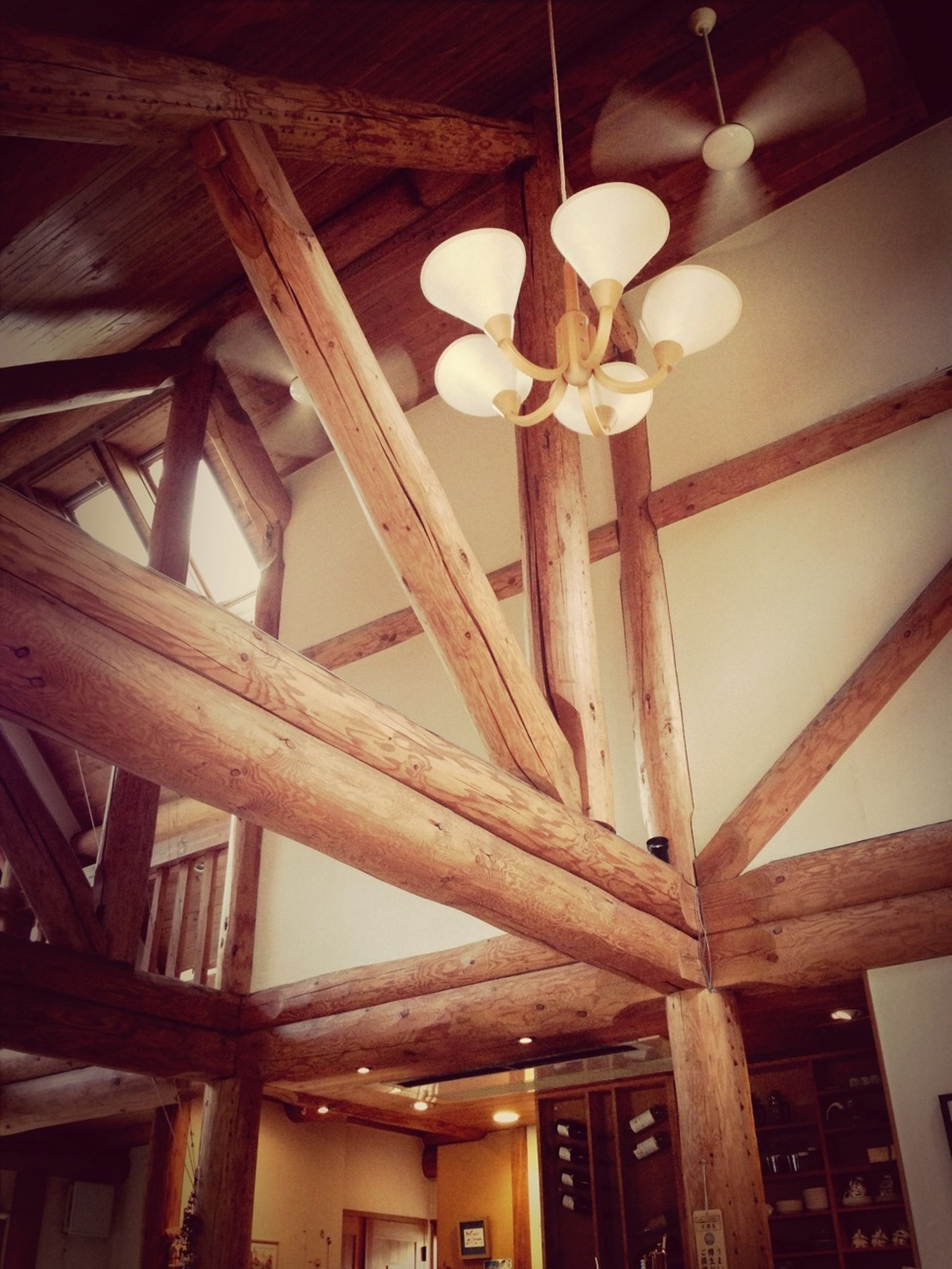 low angle view, architecture, built structure, ceiling, hanging, lighting equipment, indoors, building exterior, illuminated, no people, decoration, day, architectural column, electric lamp, architectural feature, building, wood - material, pattern
