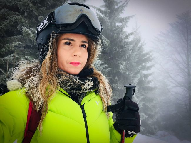 Portrait of woman wearing Uvex ski glasses and Uvex ski helmet and holding ski poles with pine cone trees covered in snow in the background Trees Evergreen Forest Skiing Ski Helmet Ski Glasses Skier Uvex Face Woman Cold Temperature Winter Weather Snow Adventure Headwear Real People Fog One Person Portrait Day Leisure Activity Sports Helmet Outdoors Nature Helmet Mountain Young Adult