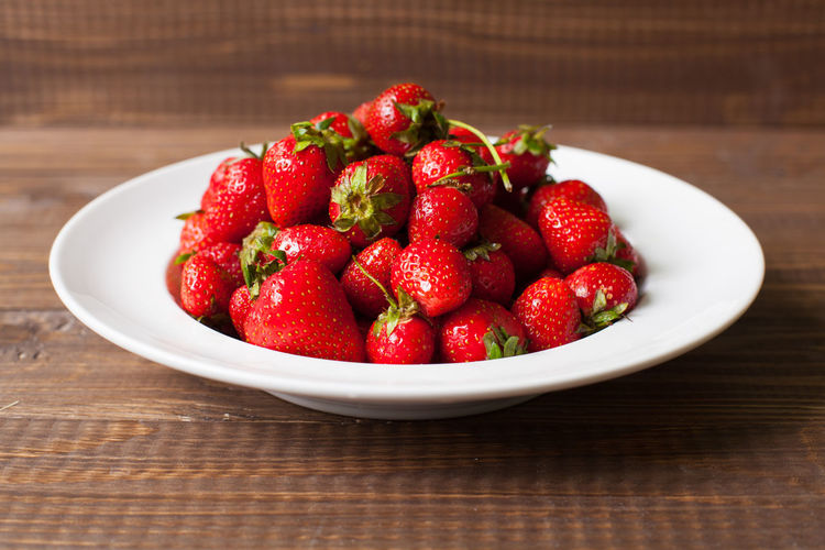 Close-up of strawberries in bowl on wooden table