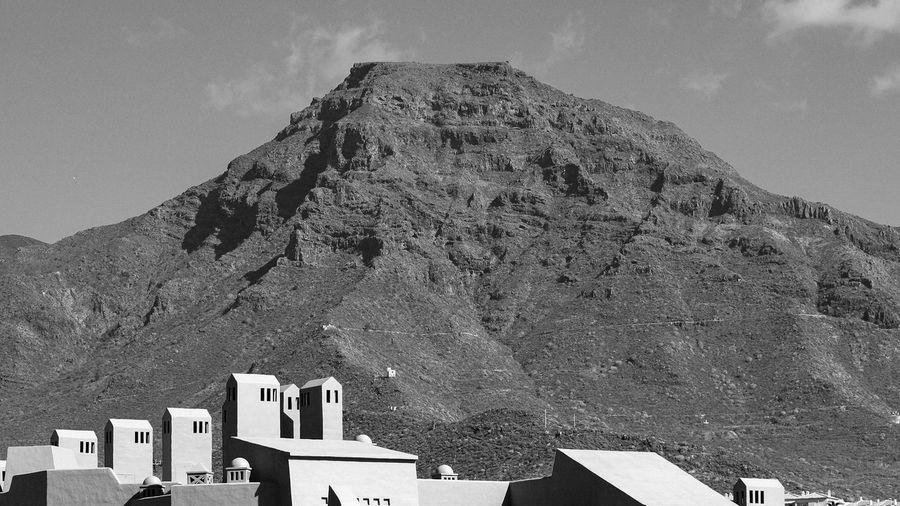 Buildings against mountain range