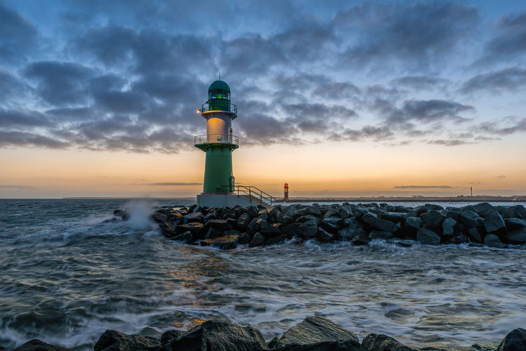 Lighthouse amidst sea against sky during sunset