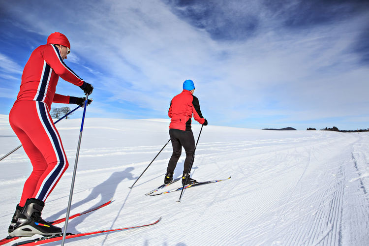 Men Skiing On Snowcapped Mountain Against Sky