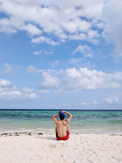 Rear view of shirtless man sitting at beach against sky