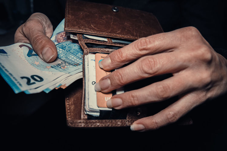 Cropped hand of woman holding purse with banknote