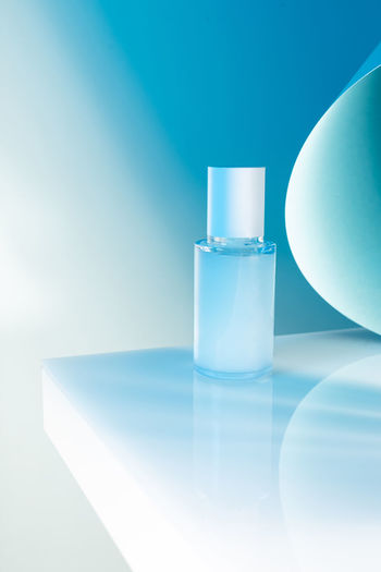 Close-up of glass bottle on table against blue background
