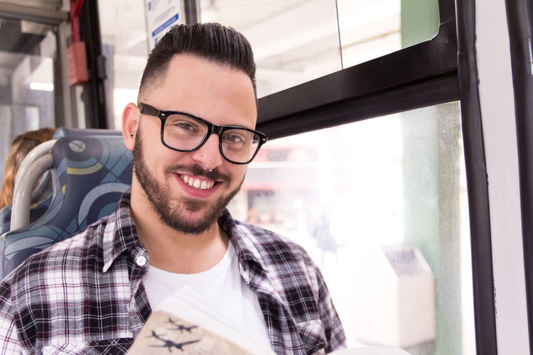 Portrait of smiling young man sitting in bus