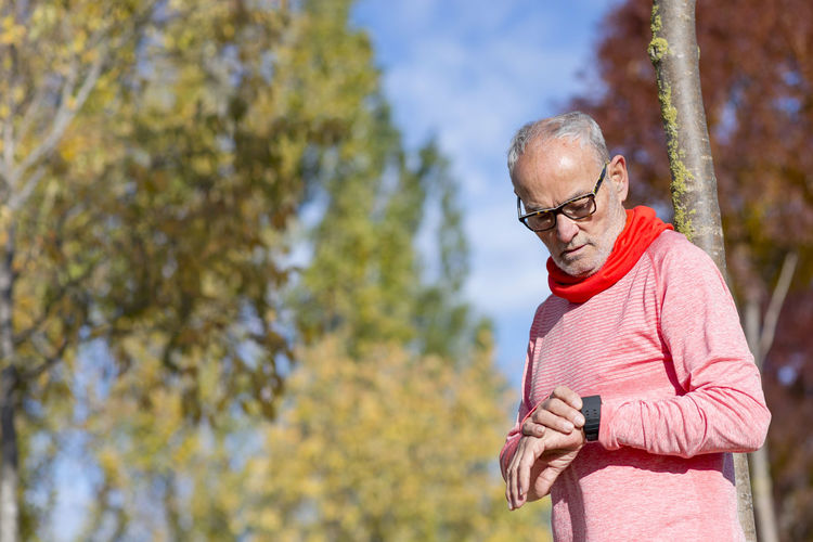 Senior man outdoors stretching and monitoring after jogging Adult Day Exercising Focus On Foreground Front View Glasses Healthy Lifestyle Leisure Activity Lifestyles Looking Mature Adult Mature Men Nature One Person Outdoors Real People Standing Tree Waist Up Wireless Technology