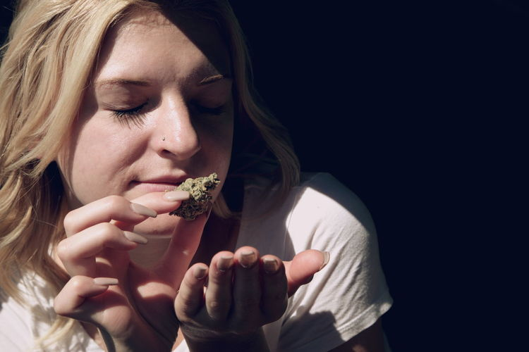 Close-Up Of Woman Smelling Cannabis Plant At Home