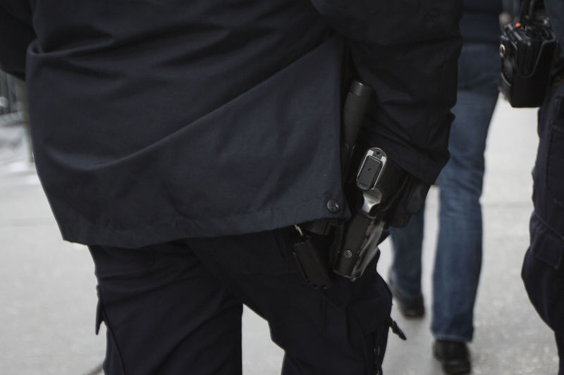 Midsection Of Men With Gun Walking On Street