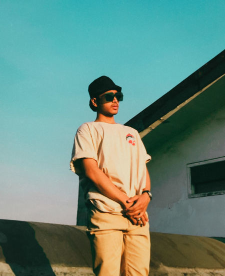 Young man wearing sunglasses standing against clear sky