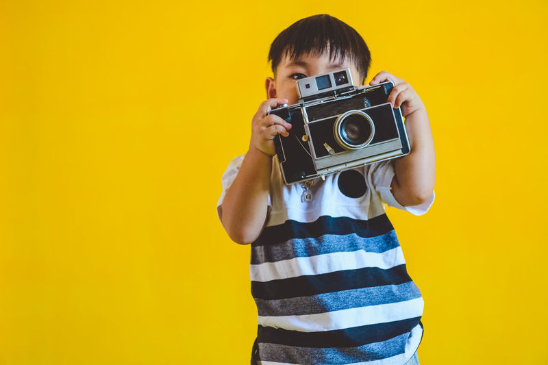 Portrait of man photographing against yellow background