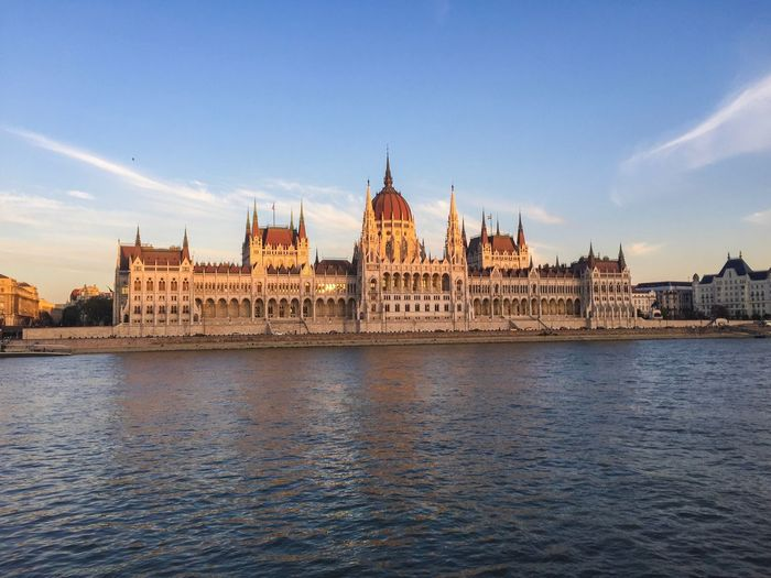 Hungarian parliament building by danube river against sky during sunset