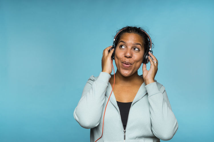 Woman Listening Music Against Blue Background