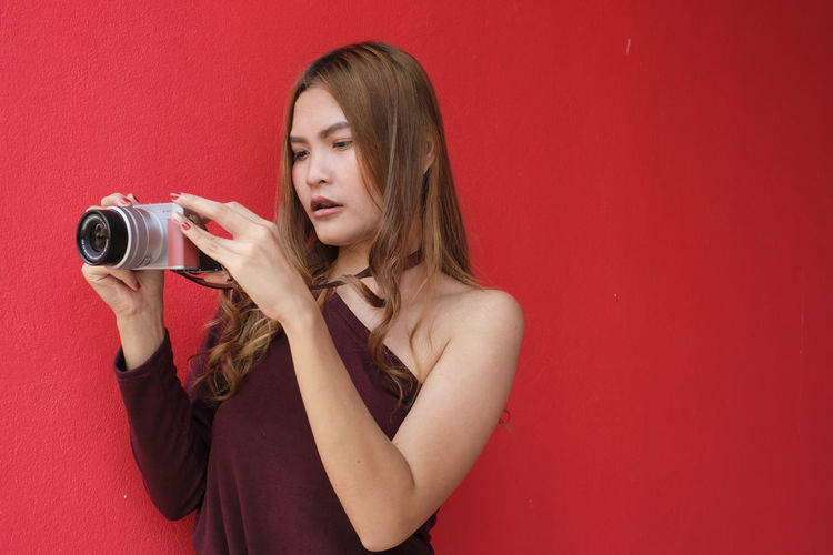 Beautiful young woman holding camera against red background
