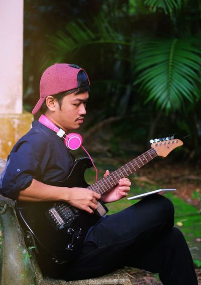 Young man playing guitar while sitting in park