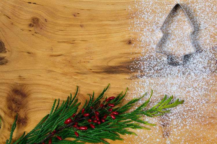 Directly Above Shot Of Pine Needles With Cookie Cutter And Flour On Wooden Table During Christmas