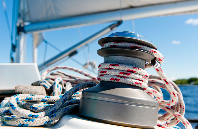 Close-up of roped rolled in bollard on sailboat against sky