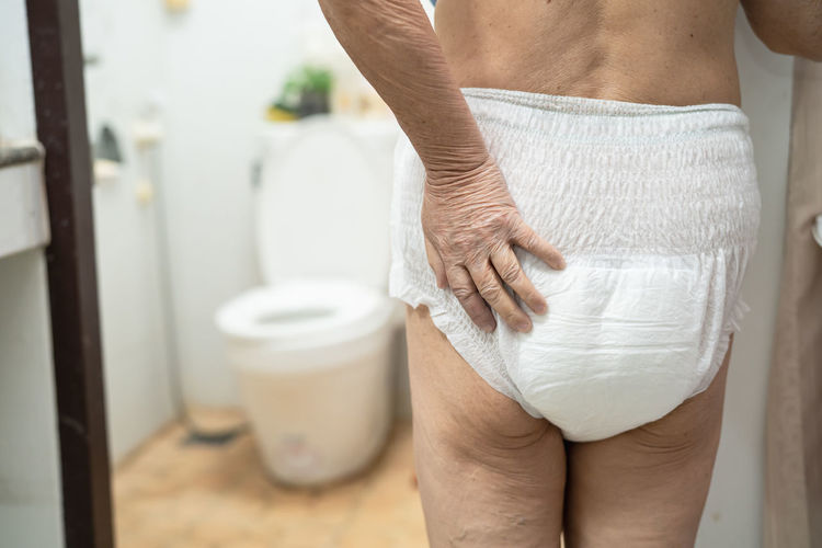 Midsection of senior woman wearing diaper in bathroom