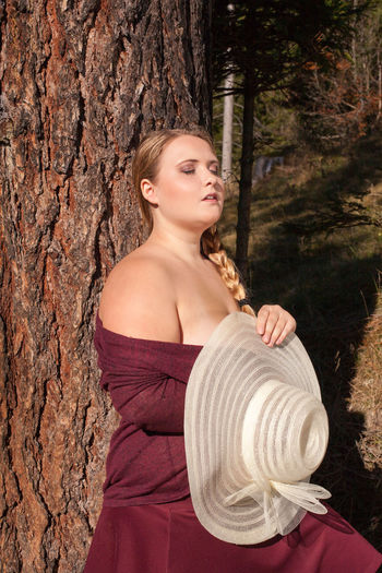 Chubby girl with blond Bunches dreaming leaning against a tree. The bare shoulders by sunbeams warmed with eyes closed and sunhat in hand. Curvy Supermodel Hair Plus Size Beauty  Self-Confidence Trends Adult Beautiful Woman Blond Hair Curvy Day Nature One Person One Young Woman Only Outdoors Overweight People Plussize Real People Sun Thick Tree Tree Trunk Well-being Young Adult Young Women