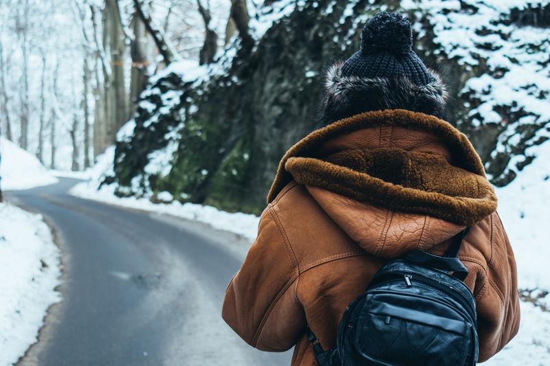 A woman with a hat, brown leather coat and backpan on, standing on a road in a winter landscape. Closeup Hat Hiking Leather Coat Lifestyles Nature Outdoors Person Road Season  Snow Warm Clothing Winter Woman On The Way