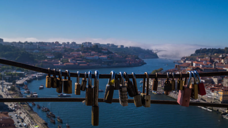 Close-up of padlocks hanging on sea at porto against sky