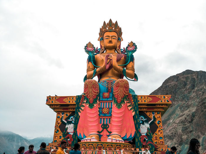The impressive 32 meter tall statue of Maitreya Buddha is visible from a distance as soon as one enters the Diskit Region. Perched atop a hillock, facing the Shyok River towards Pakistan and complementing the surroundings, Maitreya Budhha was constructed in 2006 keeping in mind three objectives - protection of Diskit Village, prevention of further war with Pakistan, and to promote world peace. The statue was inaugurated by H.H Dalai Lama in 2010. Belief Human Representation Spirituality Sky Religion Statue Representation Sculpture Art And Craft Male Likeness Place Of Worship Cloud - Sky Built Structure Architecture Creativity Building Outdoors Idol