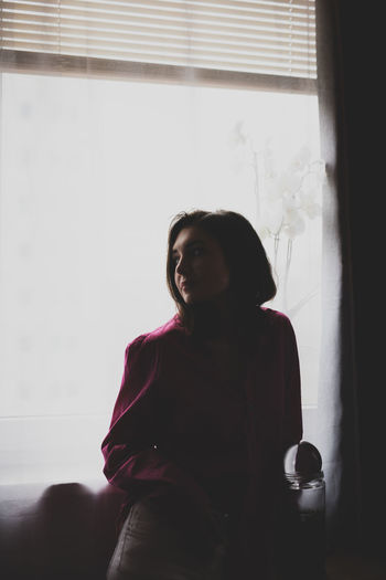 Woman looking away while standing against window