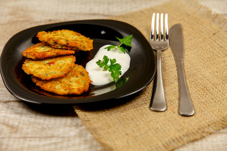 Potato pancakes with sour cream and parsley on a wooden table Homemade Meal Potato Ukrainian  Vegetarian Close-up Eating Utensil Food Food And Drink Fork Freshness Fried Garnish Healthy Eating High Angle View Household Equipment Indoors  Kitchen Utensil Meal Meat No People Place Mat Plate Potato Pancake, Ready-to-eat Sackcloth Serving Size Still Life Table Table Knife Vegetable Wellbeing