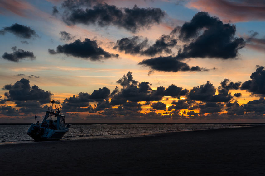 a stranded boat at low tide on the North Sea beach on Borkum at sunset Sunset Sky Cloud - Sky Water Sea Orange Color Nature Beach Outdoors Horizon Transportation Waterfront Beauty In Nature Tranquility Boat Boats And Water Nautical Vessel Tranquil Scene Scenics - Nature Blue Clouds