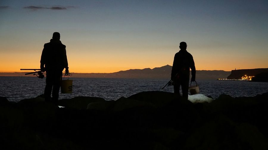Silhouette of fishermen standing by sea against sky during sunset