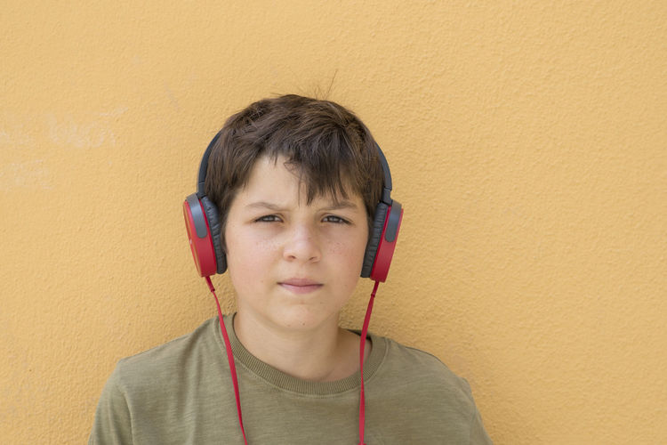 Portrait of a smiling Young boy with red headphones Boys Child Childhood Connection Front View Headphones Headshot Holding Indoors  Innocence Leisure Activity Listening Looking At Camera Males  Men Music One Person Portrait Technology Wall - Building Feature