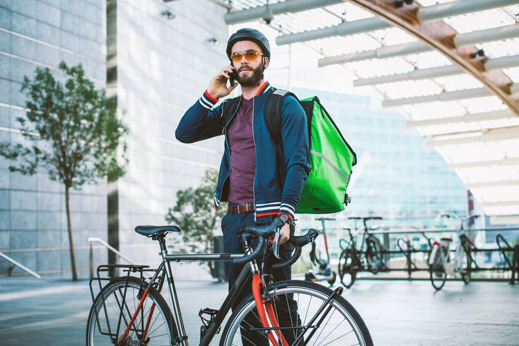 Man standing with bicycle on street in city