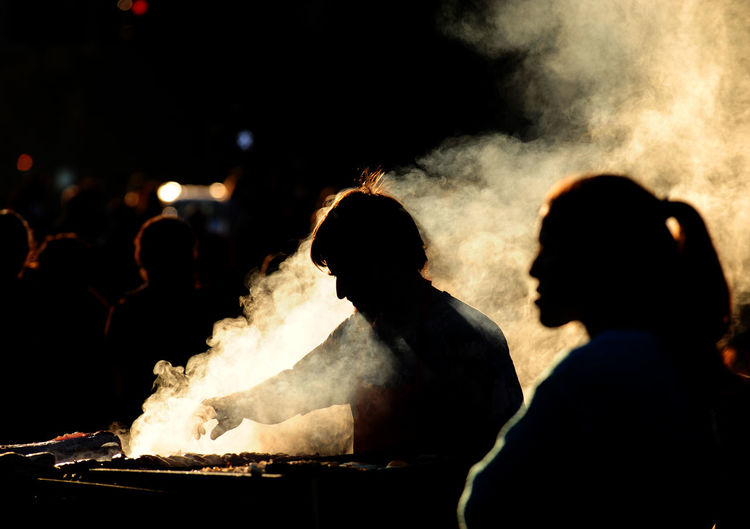 Silhouette man standing with people while preparing food on barbecue grill amidst smoke