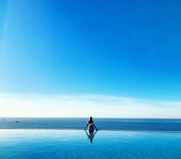 Rear view of young woman standing in infinity pool against blue sky