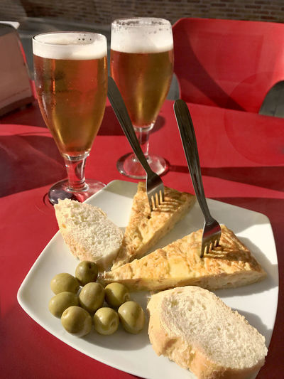 Beers with tapas of olives and Spanish tortilla Alcohol Appetizer Beer Chair Close-up Drink Drinking Glass Food Food And Drink No People Olive Plate Ready-to-eat Red Color Refreshment Snack Table Taking Photos Tortilla Tortilla Española