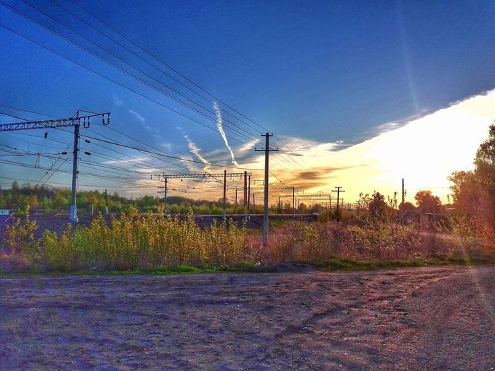 Electricity pylons on field against sky at sunset