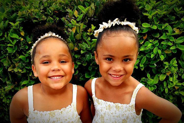 Portrait Of Happy Siblings Against Plants